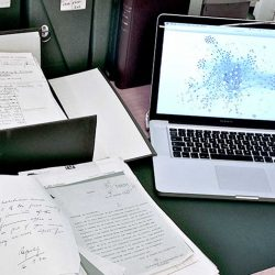View of desk: on left, documents in open archival box and on desk; on right, laptop with network visualization diagram